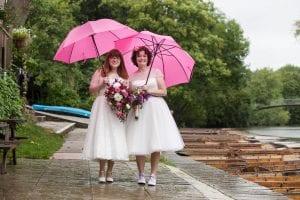 Lesbian brides in wedding dresses standing under pink umbrellas