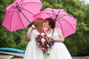 Lesbian couple in wedding dresses kissing under pink umbrellas