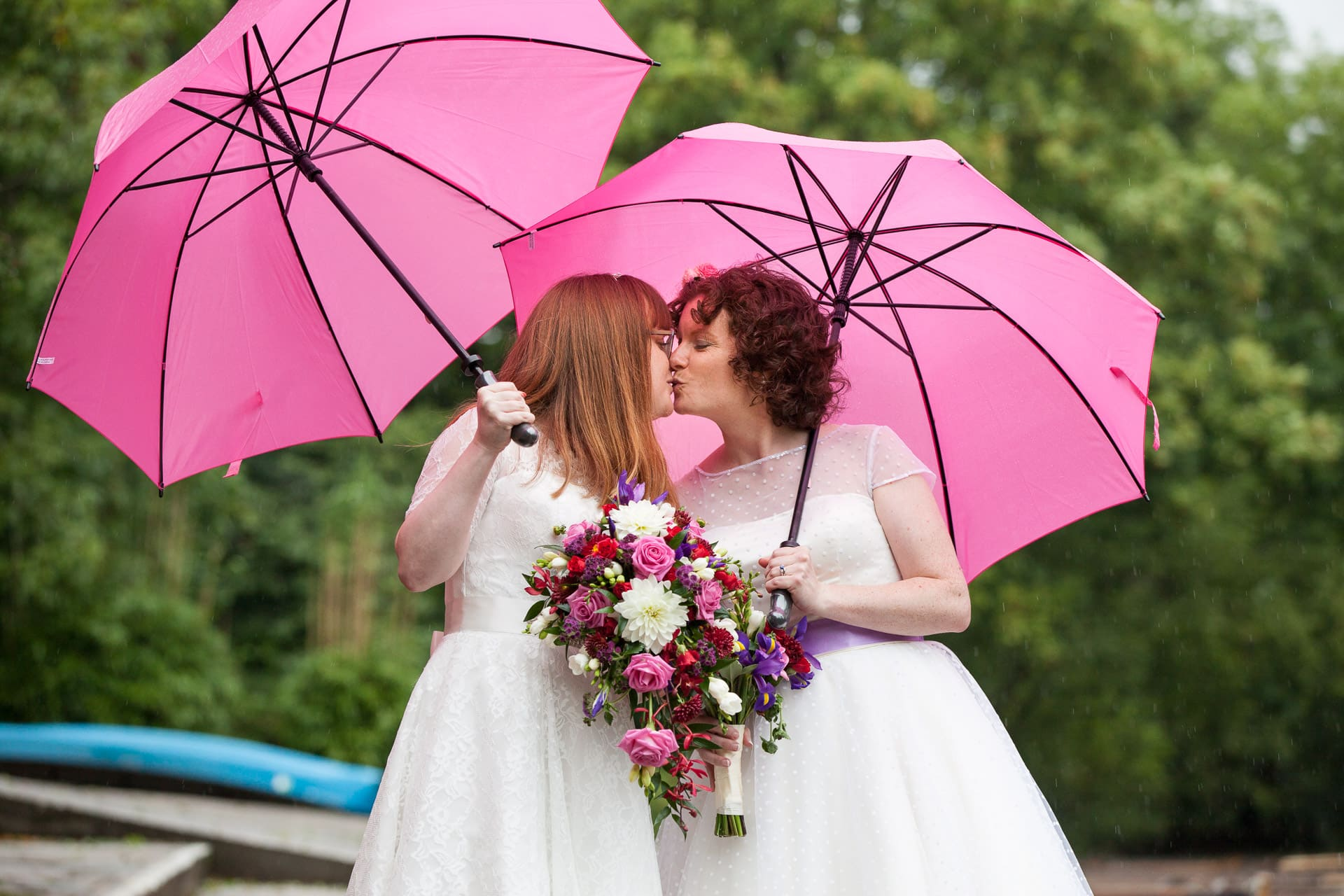 Lesbian couple in wedding dresses kissing under pink umbrellas