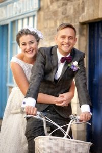 Smiling bride and groom on a custom made tandem bicycle