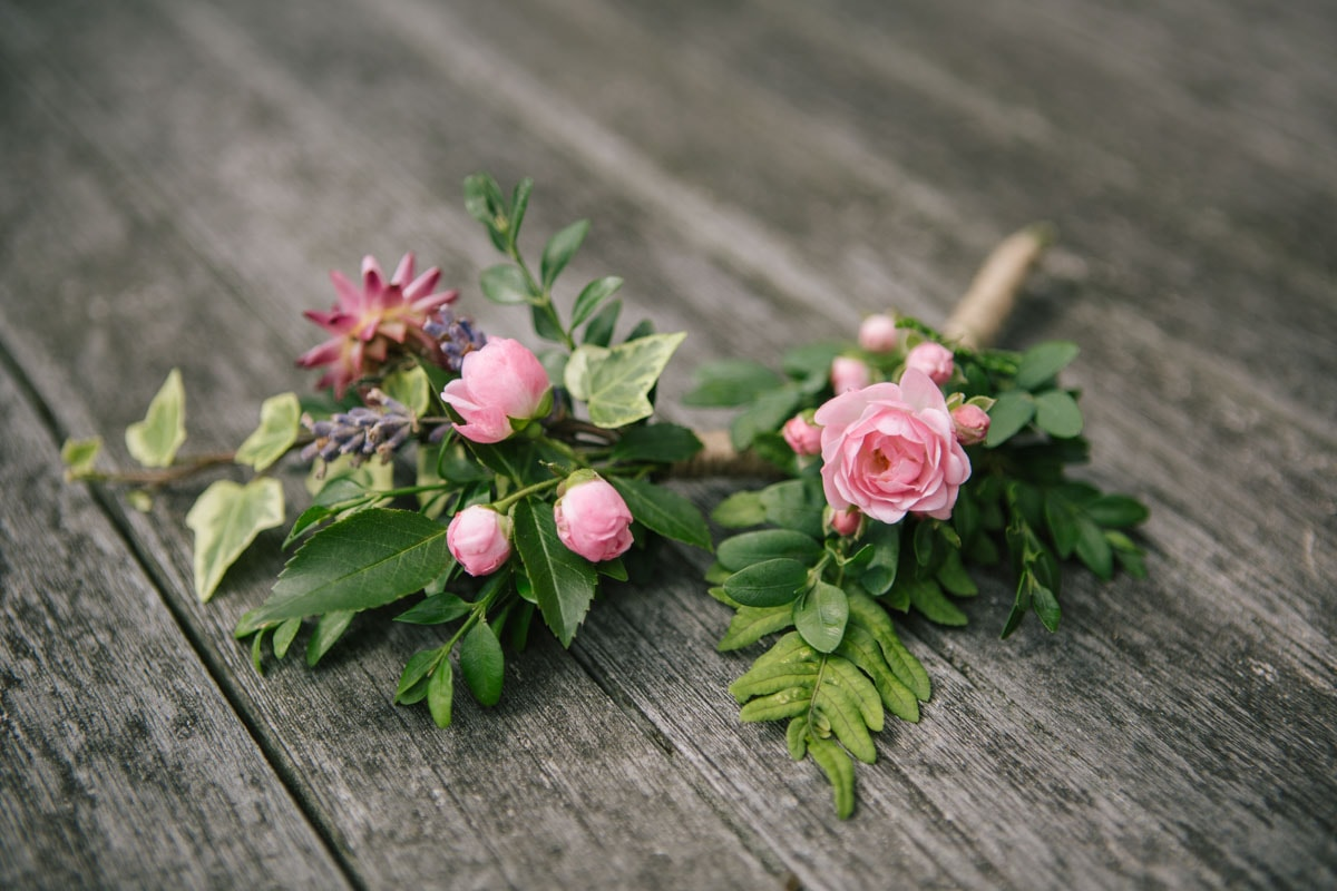 A close up of the buttonholes - pale pink blossoms and lush green leaves