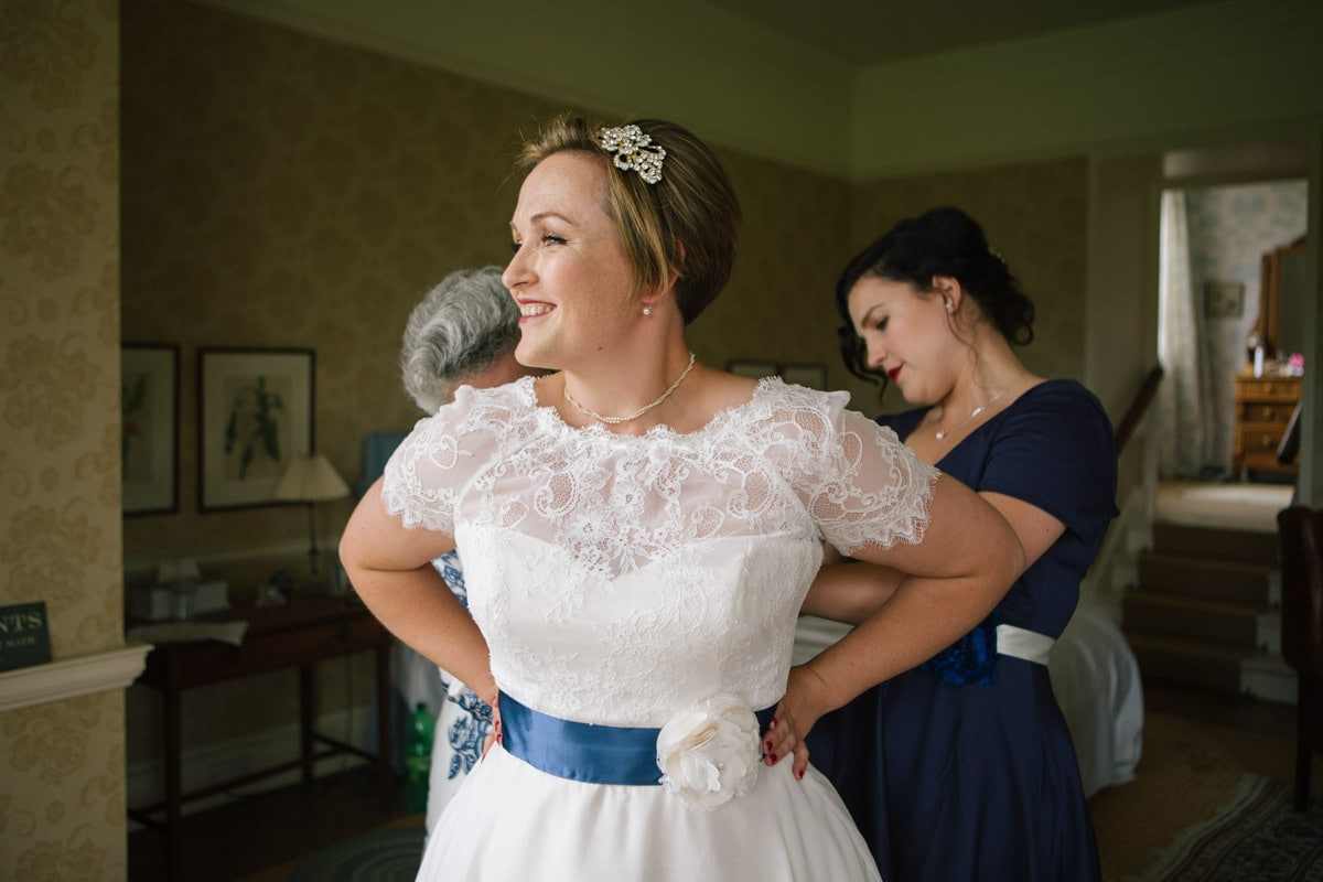 Bride Julia smiles as her mum and bridesmaid help her into her dress.
