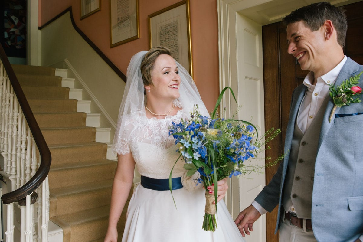 The groom sees his bride for the first time, at the bottom of the sweeping staircase in Baldon House
