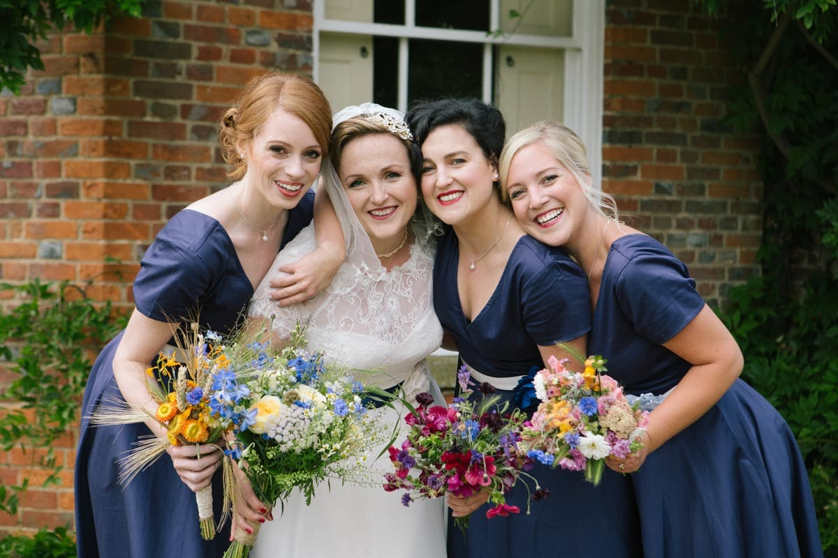 The bride and her bridesmaids smile together before the ceremony