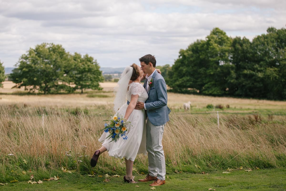 The bride steals a kiss during the couple's portrait shoot in the Oxfordshire countryside