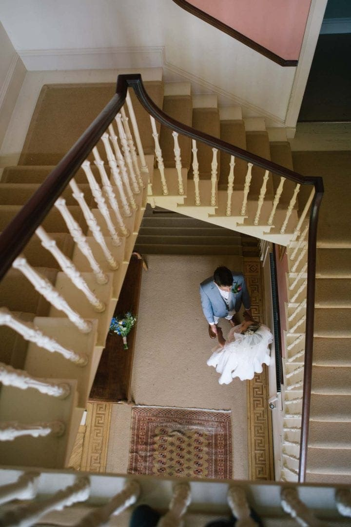 bride and groom at the bottom of a staircase at Baldon House