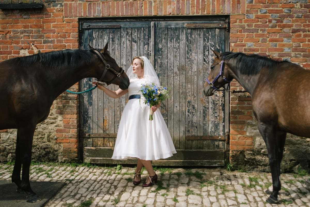 The bride says hello to two horses in the courtyard, stroking one on the nose