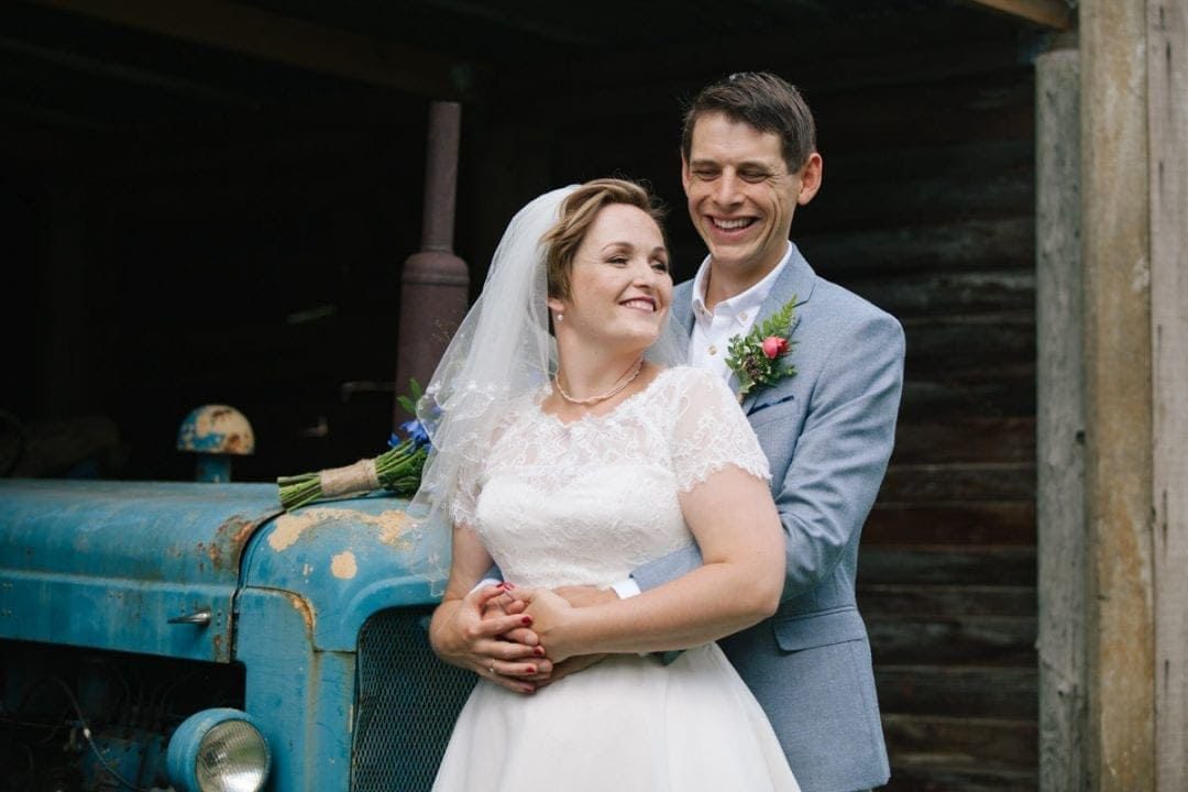groom holding bride and smiling against a blue tractor
