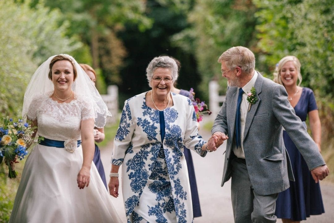 bride walking to an outdoor wedding with her smiling parents