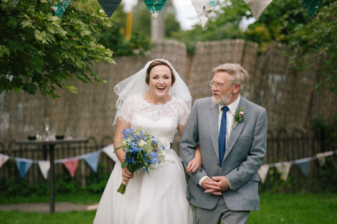 Father of the bride walking down outdoor aisle, bride smiling