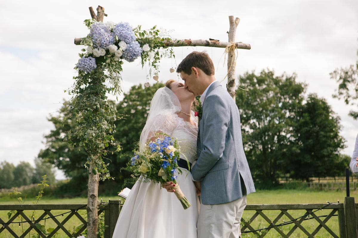 Bride and groom kiss at their garden wedding ceremony, in front of a wooden archway decorated with pale blue, lilac and white flowers