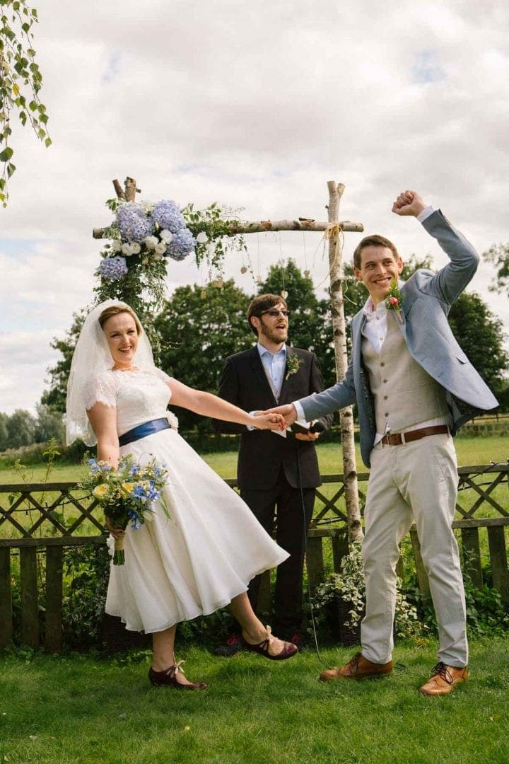 Bride and groom saying vows under a flowery alter at an outdoor wedding