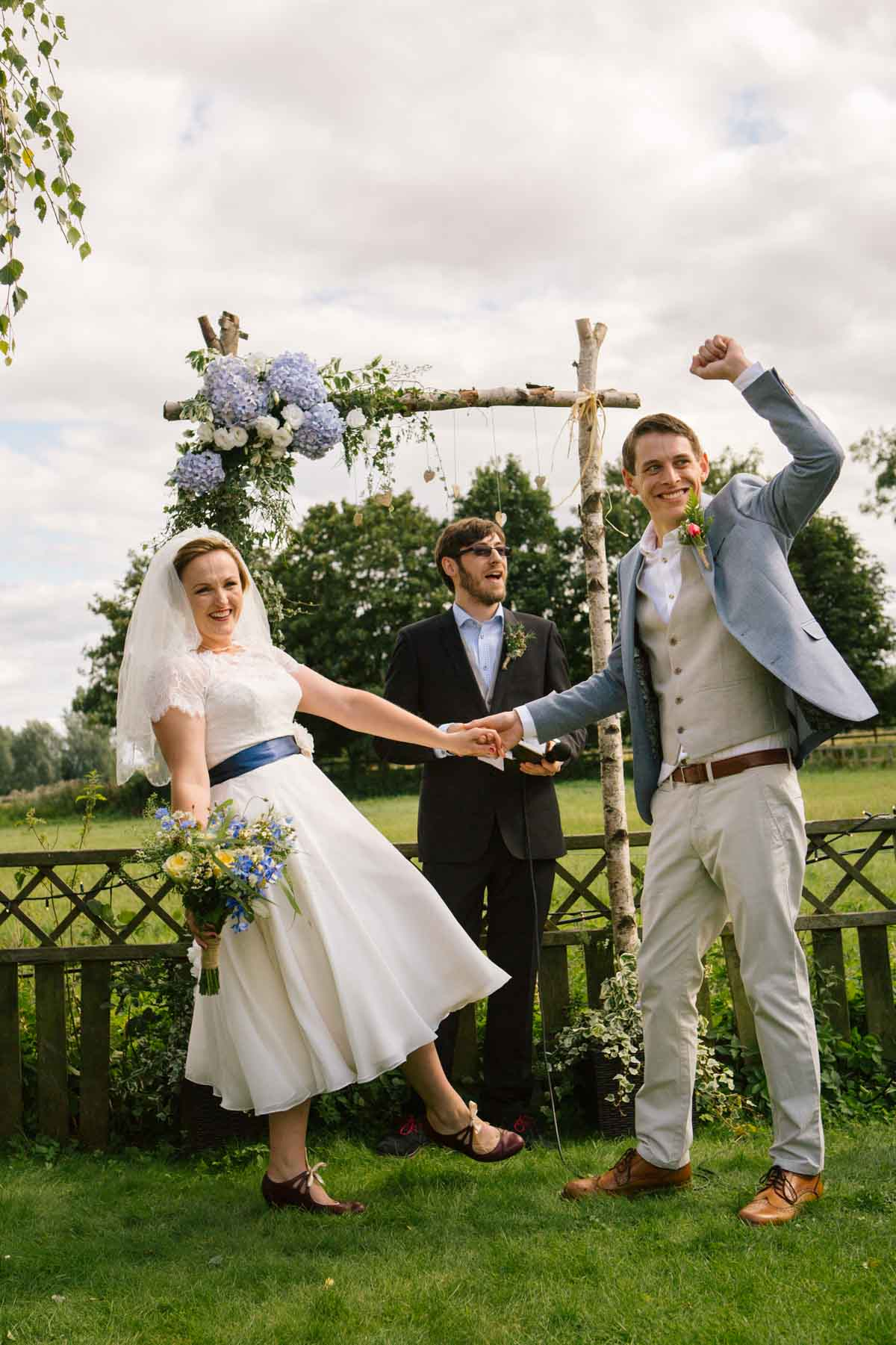 That 'Just Married' feeling. The groom punches the air while the bride laughs