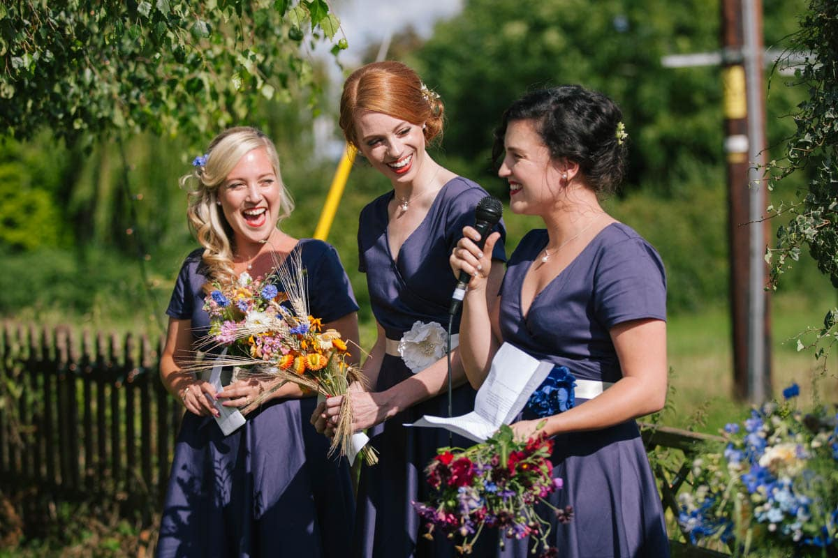 The three bridesmaids do a reading during the ceremony while holding their colourful homegrown flowers