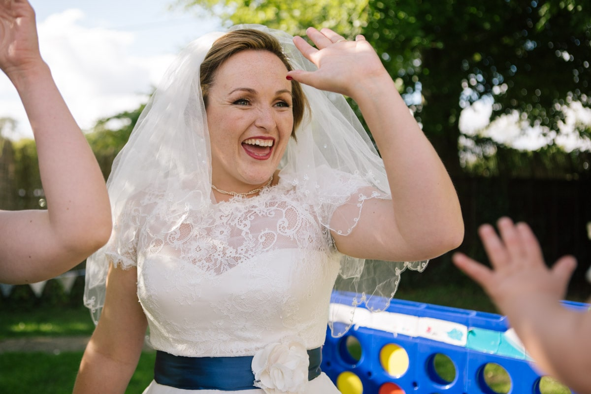 The bride is caught mid-high-five after a game of giant connect 4