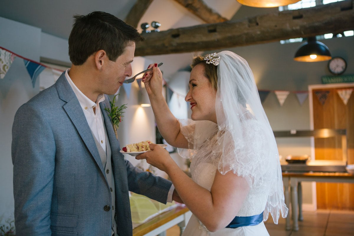 The bride feeds her groom a slice of cake