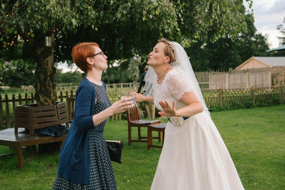Bride and her best friend blowing kisses at each other