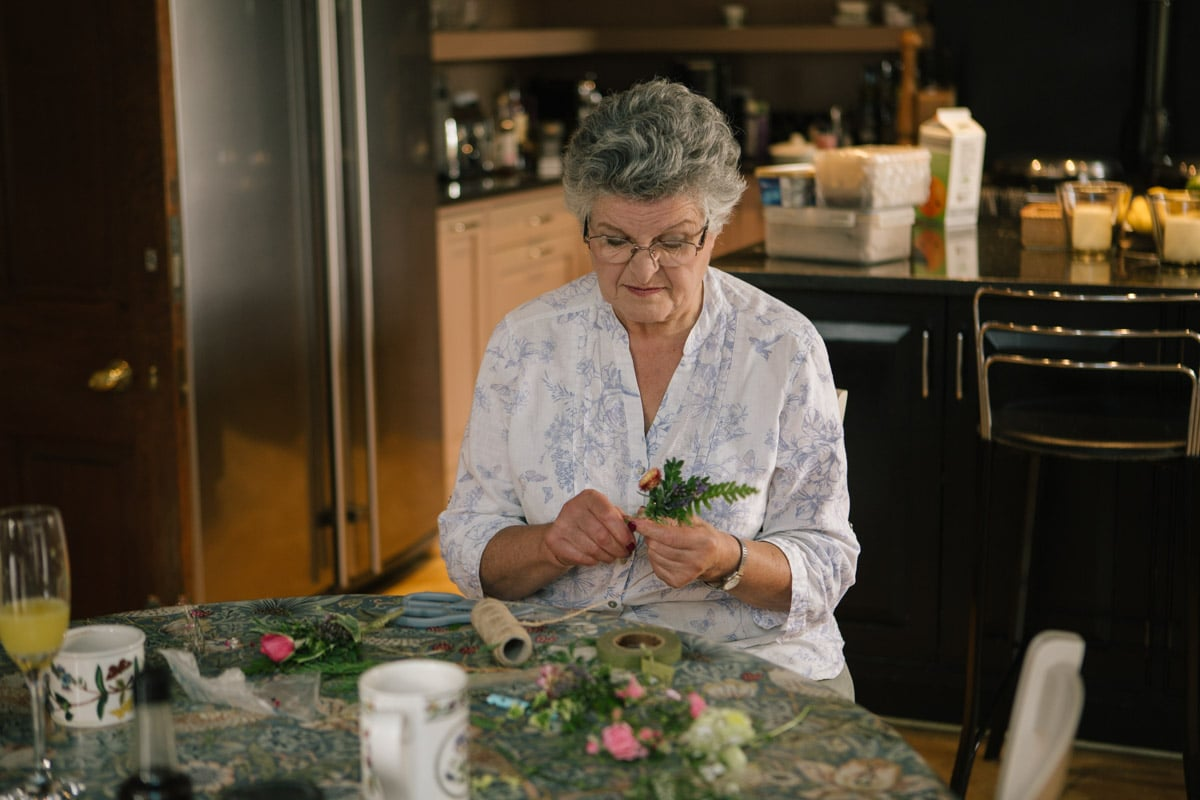 The bride's mother finishes off the buttonholes while sitting at the kitchen table