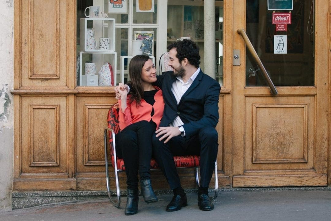 Couple sitting on a bench on a cobbled street in Paris