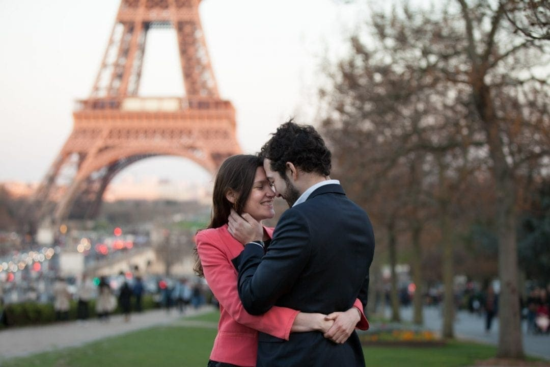 Couple cuddling in front of the Eiffel Tower