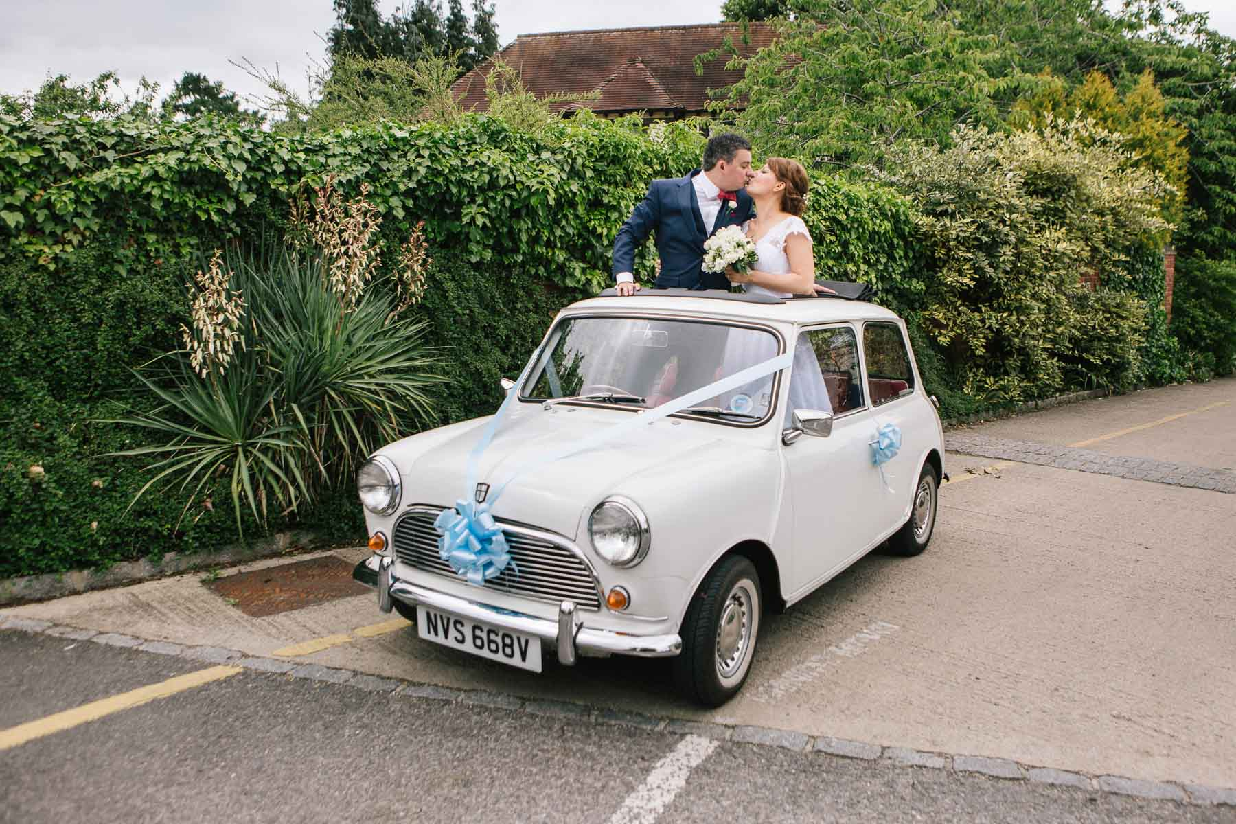 couple in a vintage Mini on their wedding day kissing