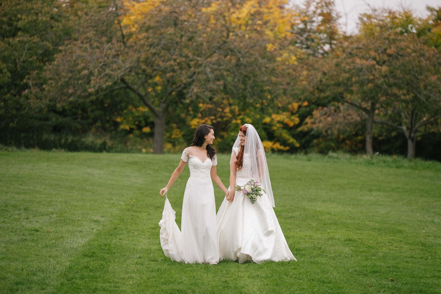 Same-sex bridal couple walk hand in hand through a Brighton park with autumnal trees in the background