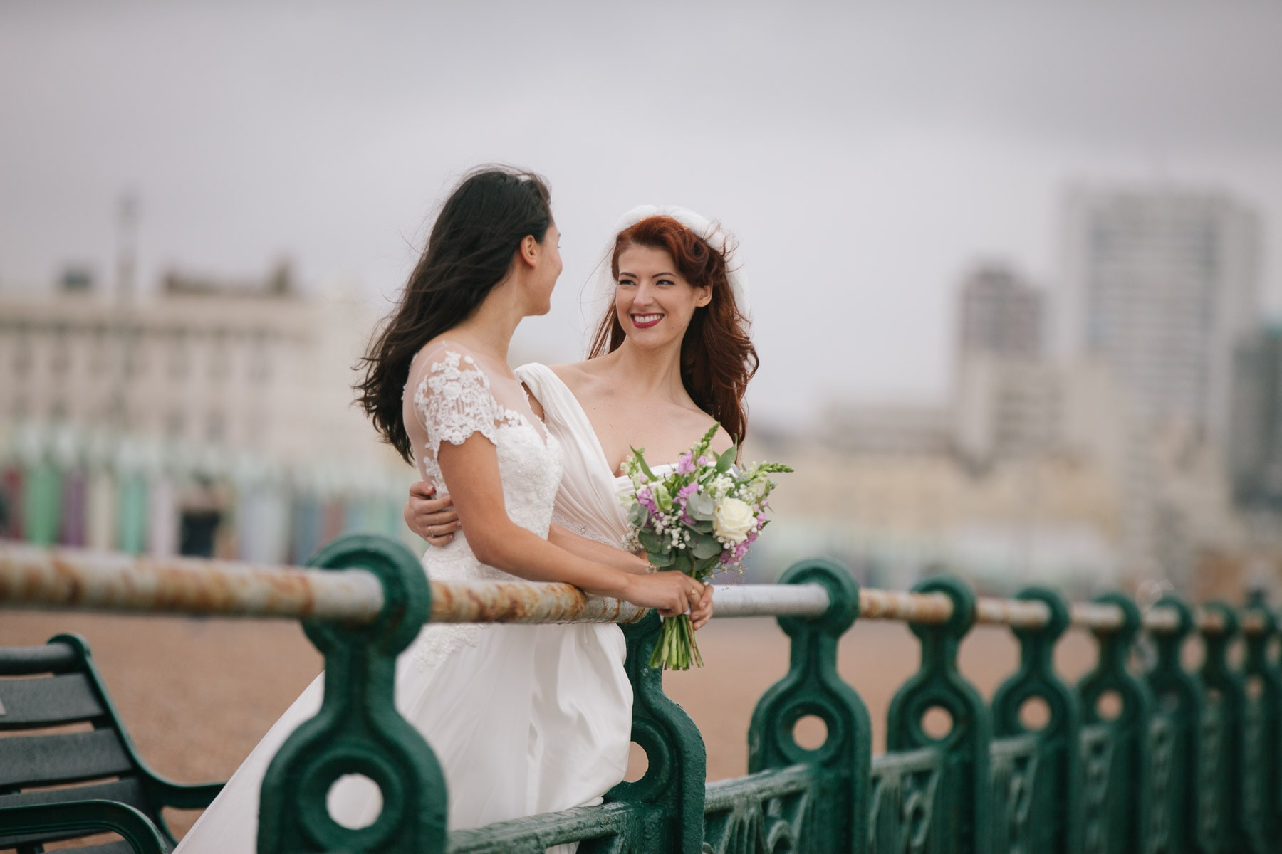 The bridal couple gaze at each other on Brighton promenade. Claudia holds the bouquet