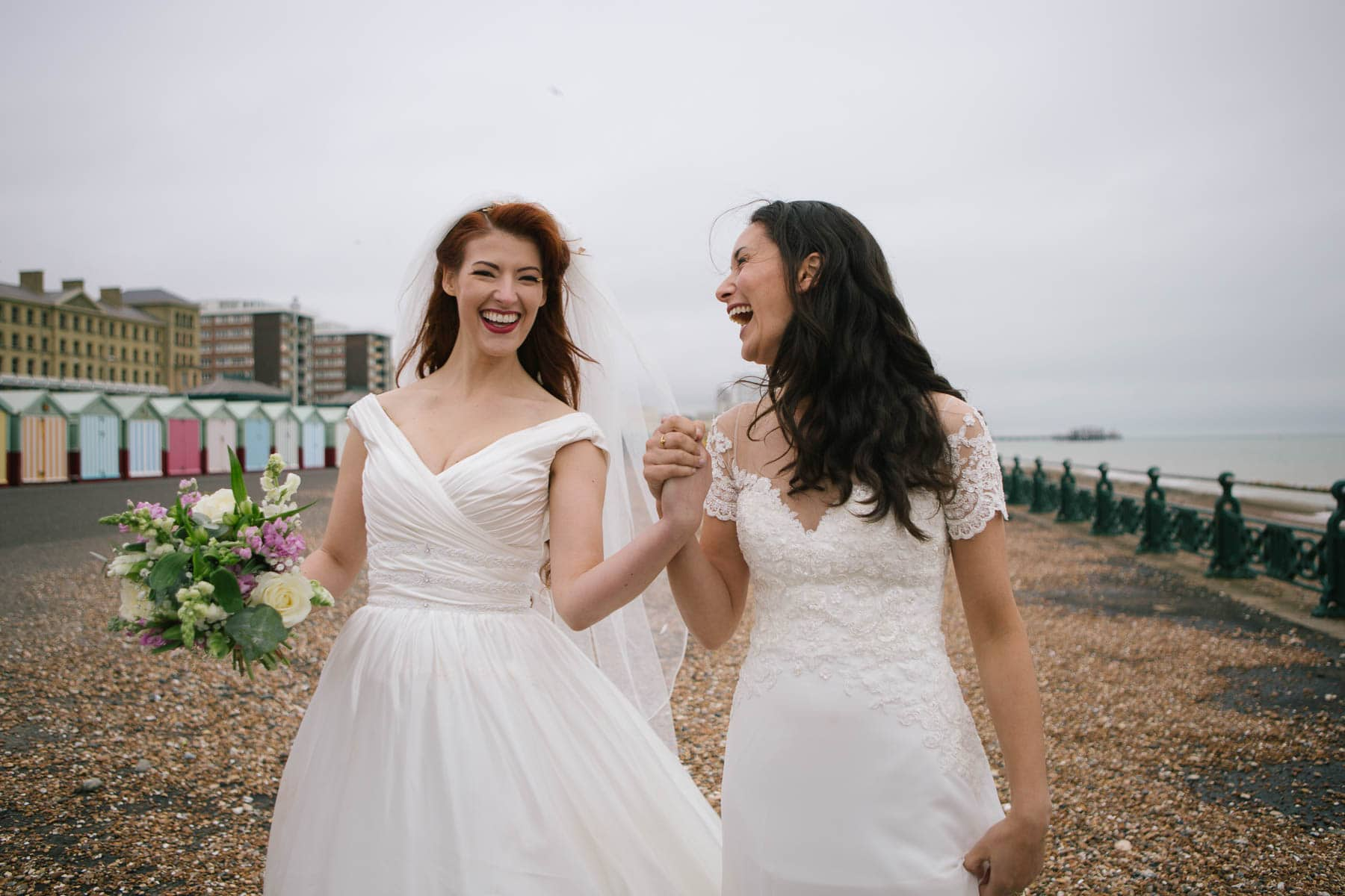 Same sex bridal couple Jessica and Claudia walk along Brighton beach holding hands