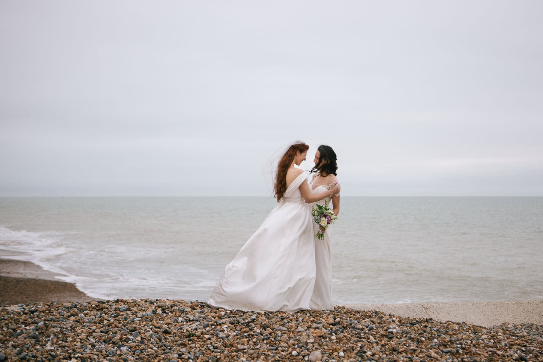 Jessica and Claudia embrace at the water's edge on Brighton beach