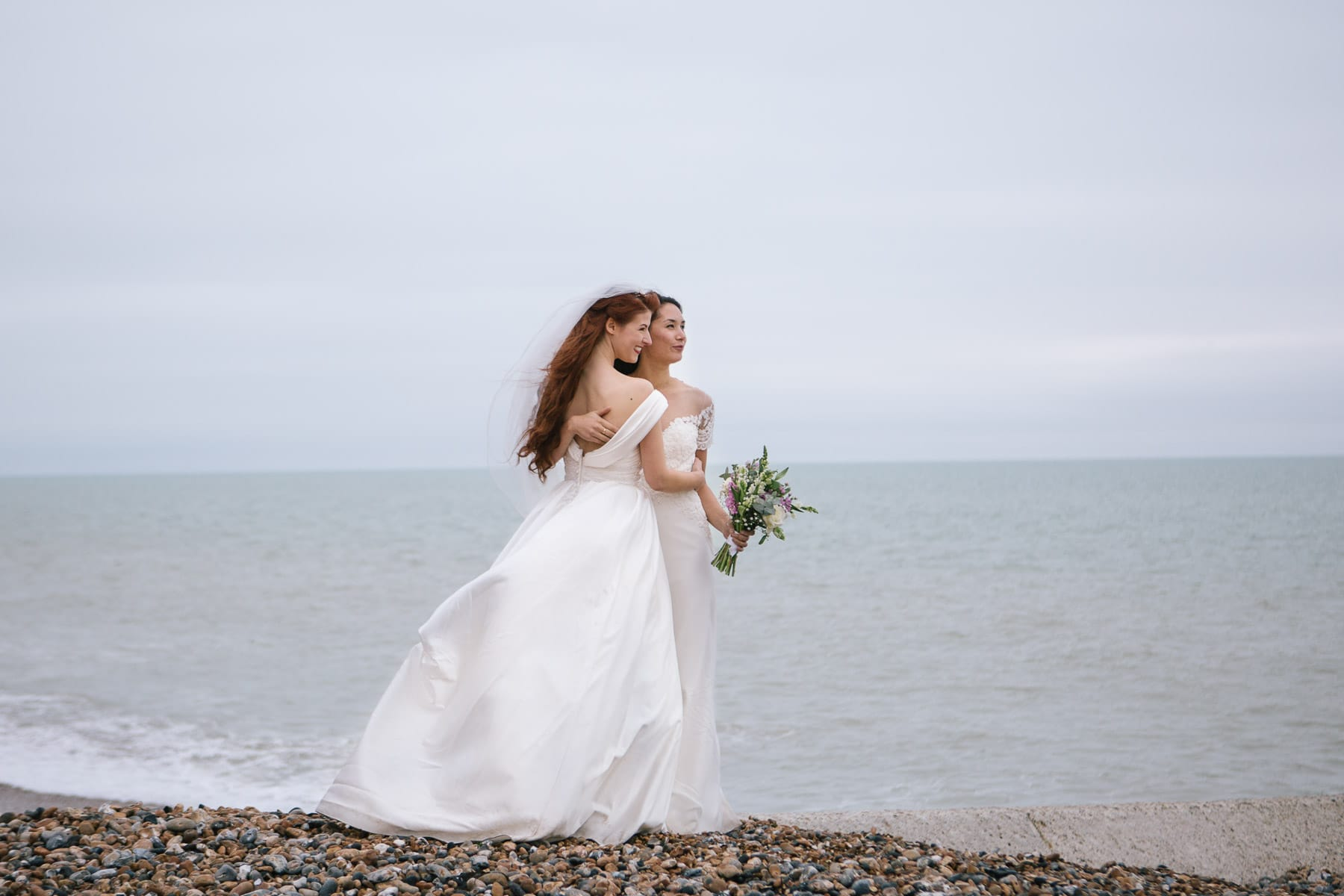 The bridal couple hold each other close while looking out to sea