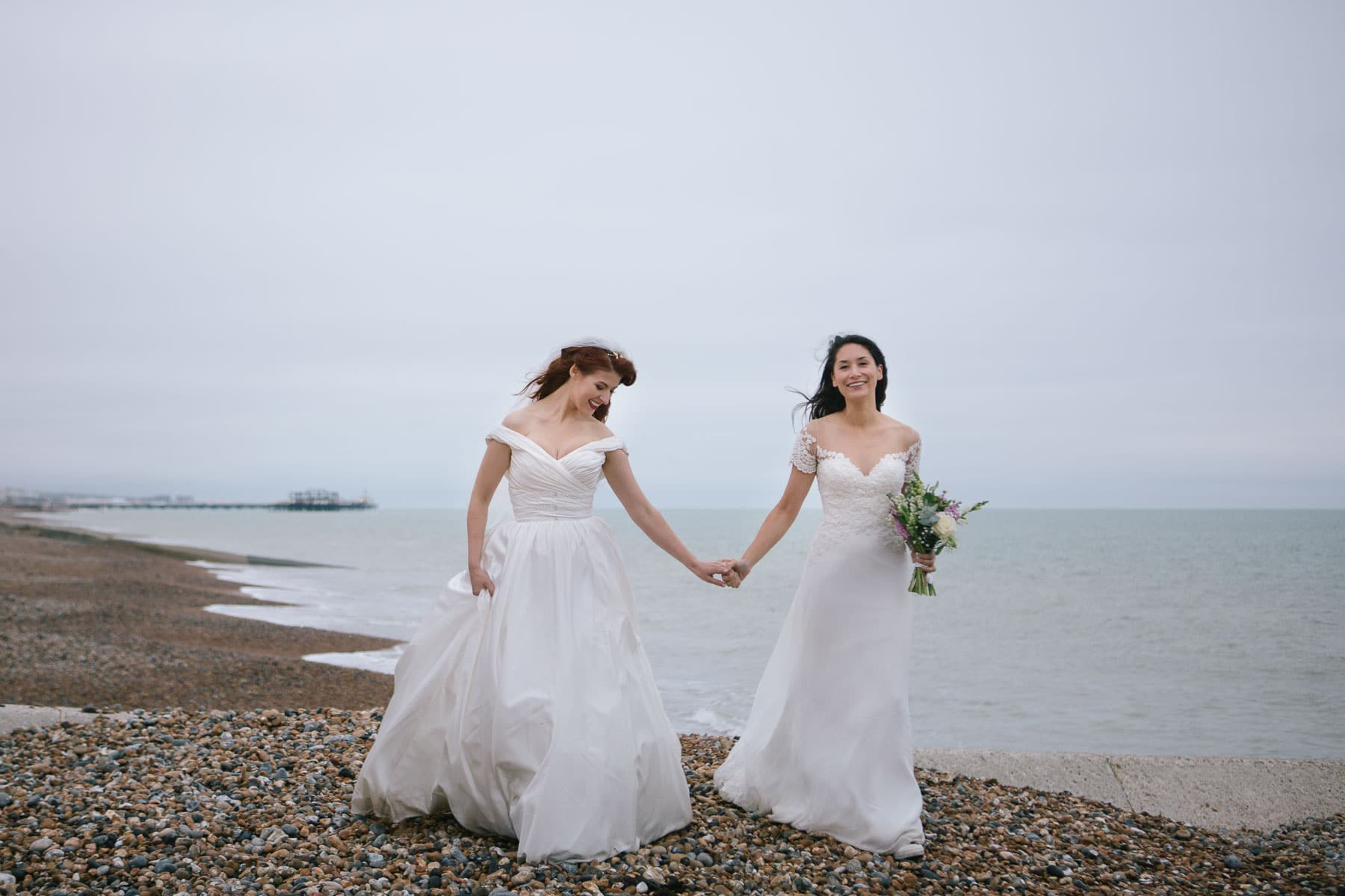lesbian brides in on Brighton Beach holding hands