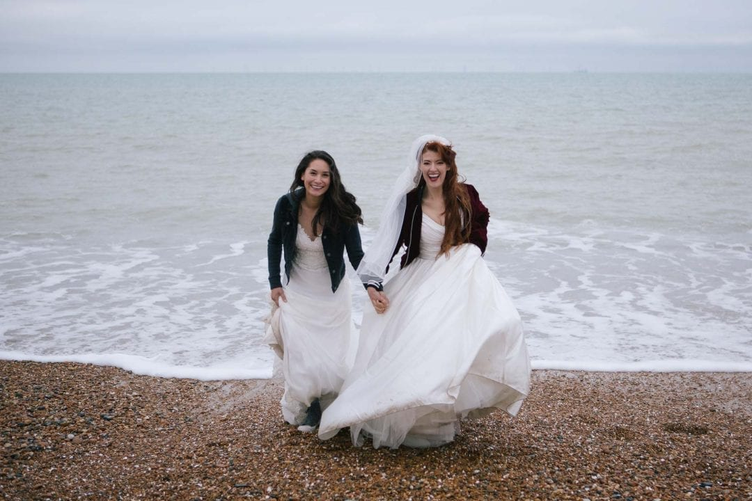 lesbian brides playing in the waves