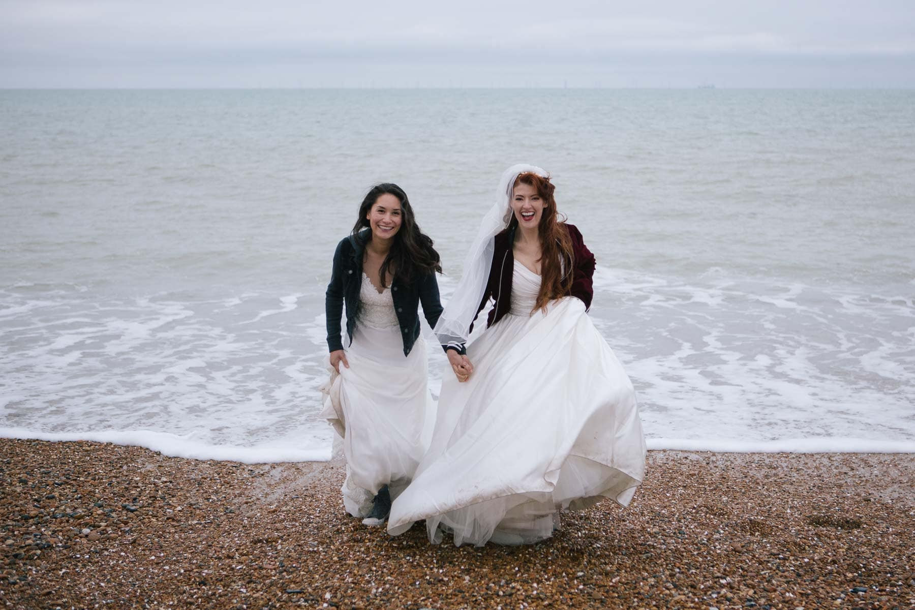 The bridal couple risk wet feet as they pose with their backs to the incoming tide