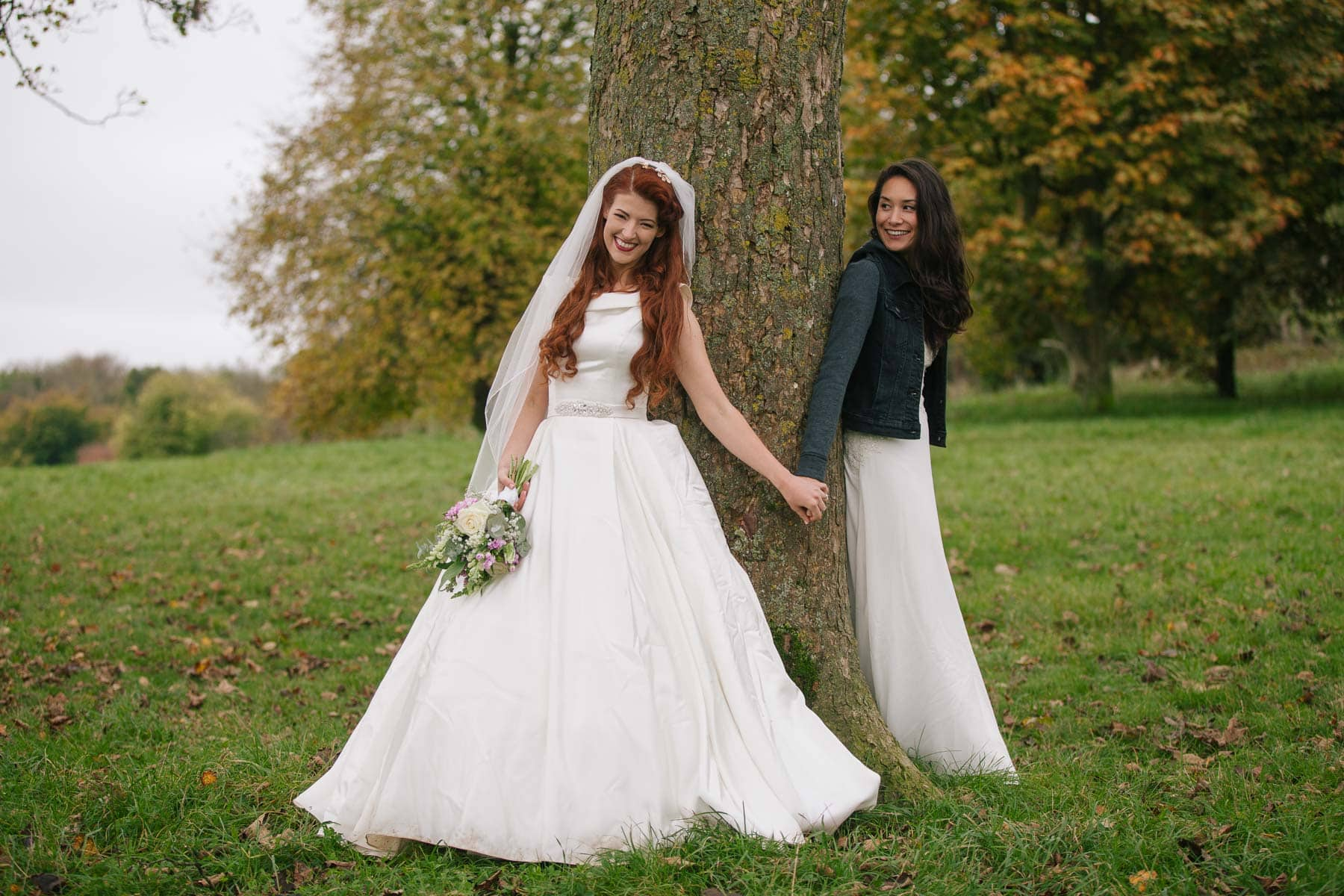 Same-sex couple Jessica and Claudia hold hands and lean against a tree