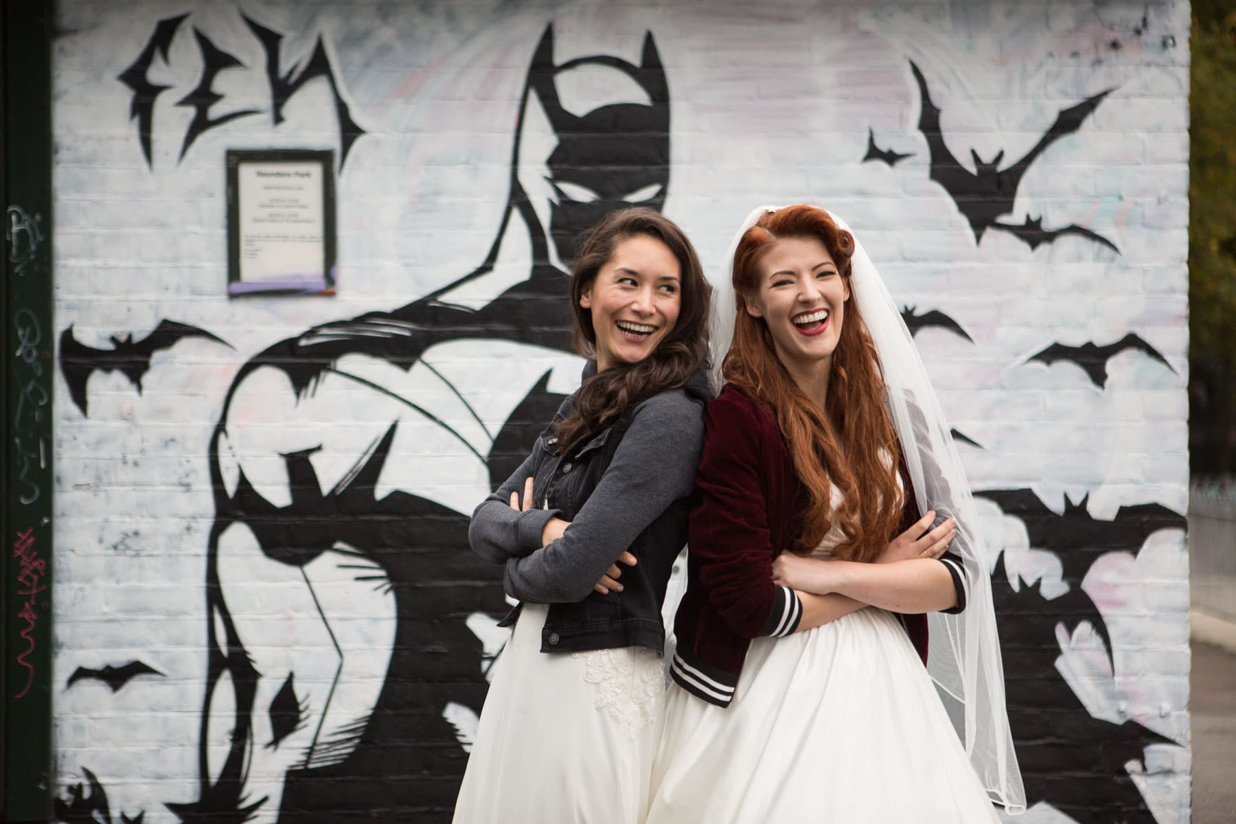 Lesbian brides in wedding dresses and bomber jackets pose back to back in front of Batman mural