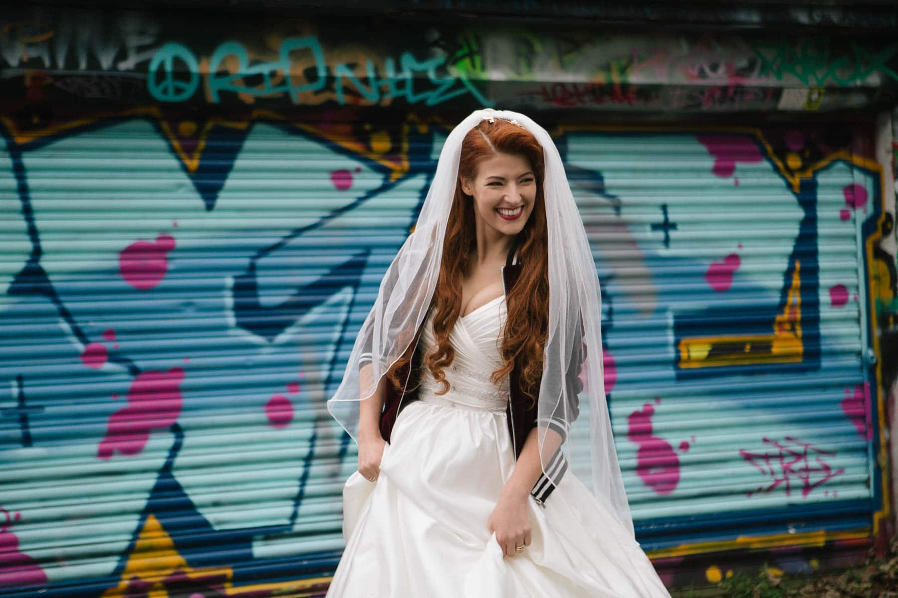 Bridal portrait of Jessica Kellgren-Fozard in front of colourful mural