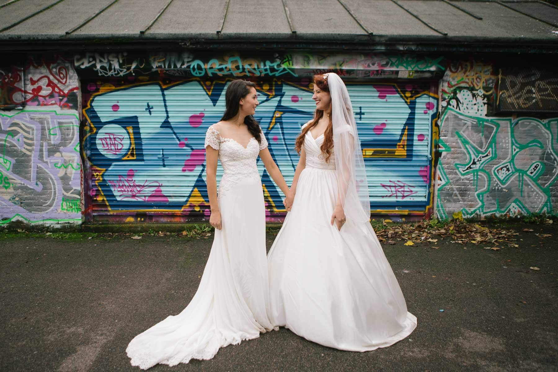 Bridal portrait of Jessica and Claudia standing in front of colourful Brighton street art. Jessica wears a 50s style Lou Lou Bridal dress, and Claudia wears a bespoke gown from White Leaf Bridal