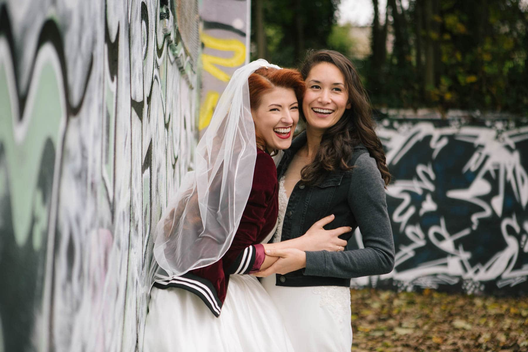 Jessica leans into her wife and the couple laugh, while posing against a graffiti wall in Brighton