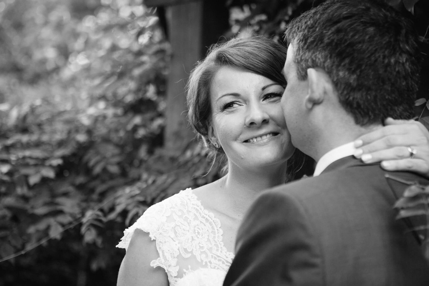 Black and white shot, groom kisses bride on cheek