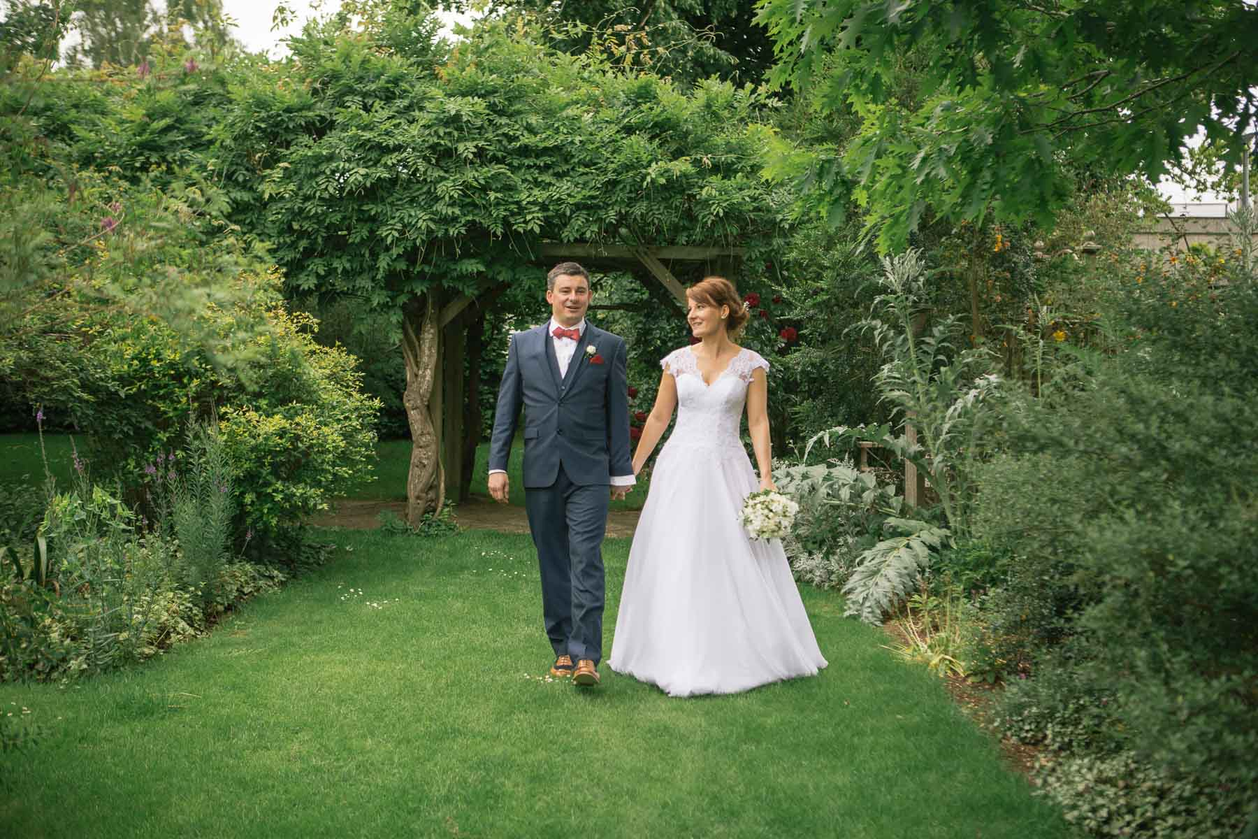 Bride and groom stand together in grounds of boathouse