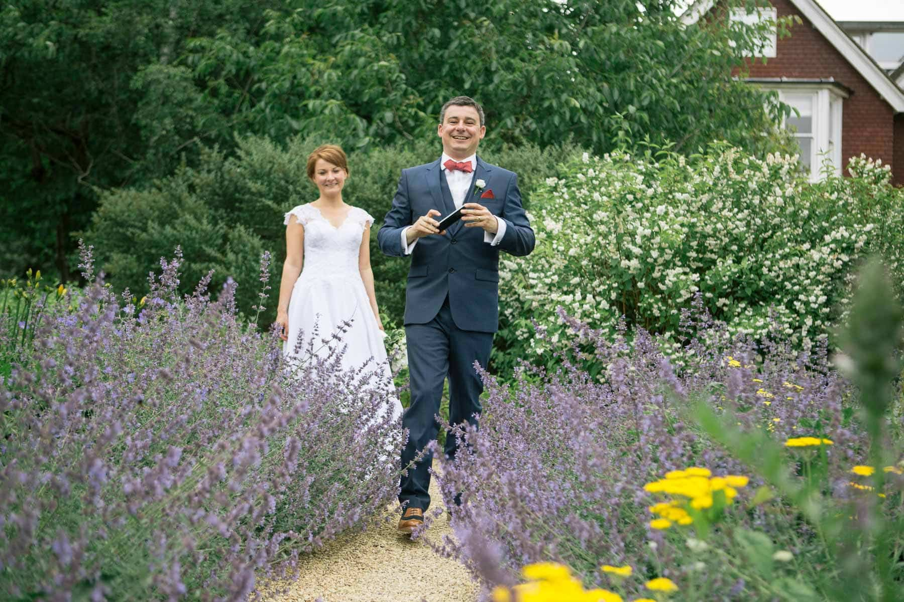 Bride and groom laughing together among lavender bushes