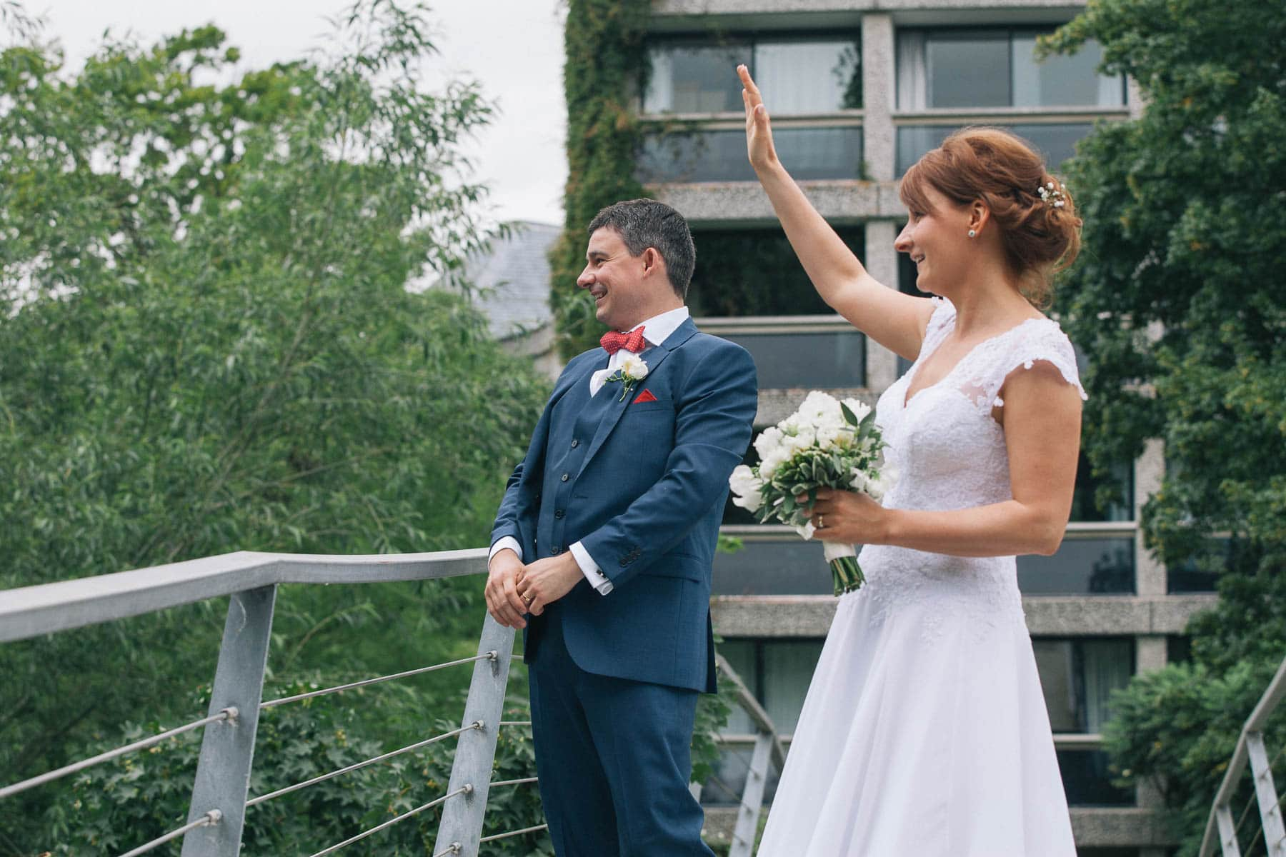 Bride and groom wave to their guests from a bridge