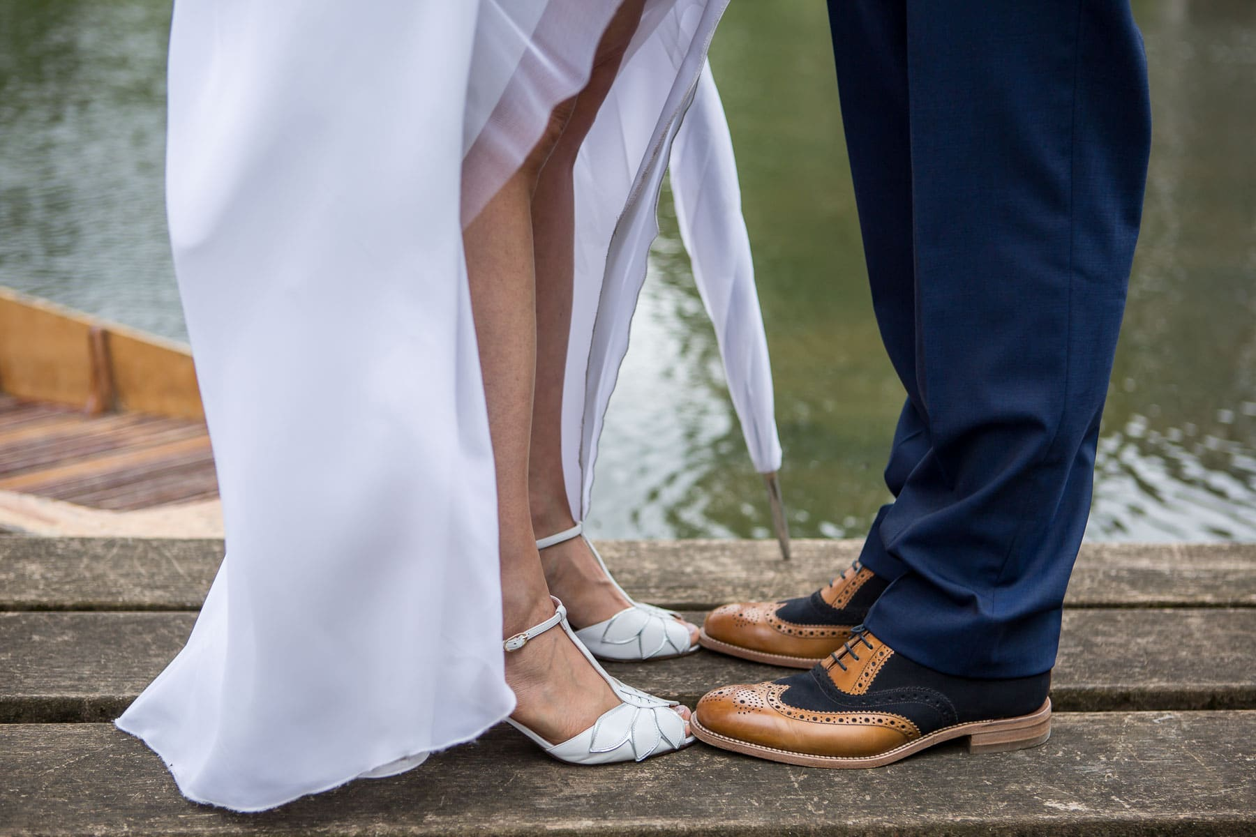 Shot of bride and groom's shoes while standing at the water's edge