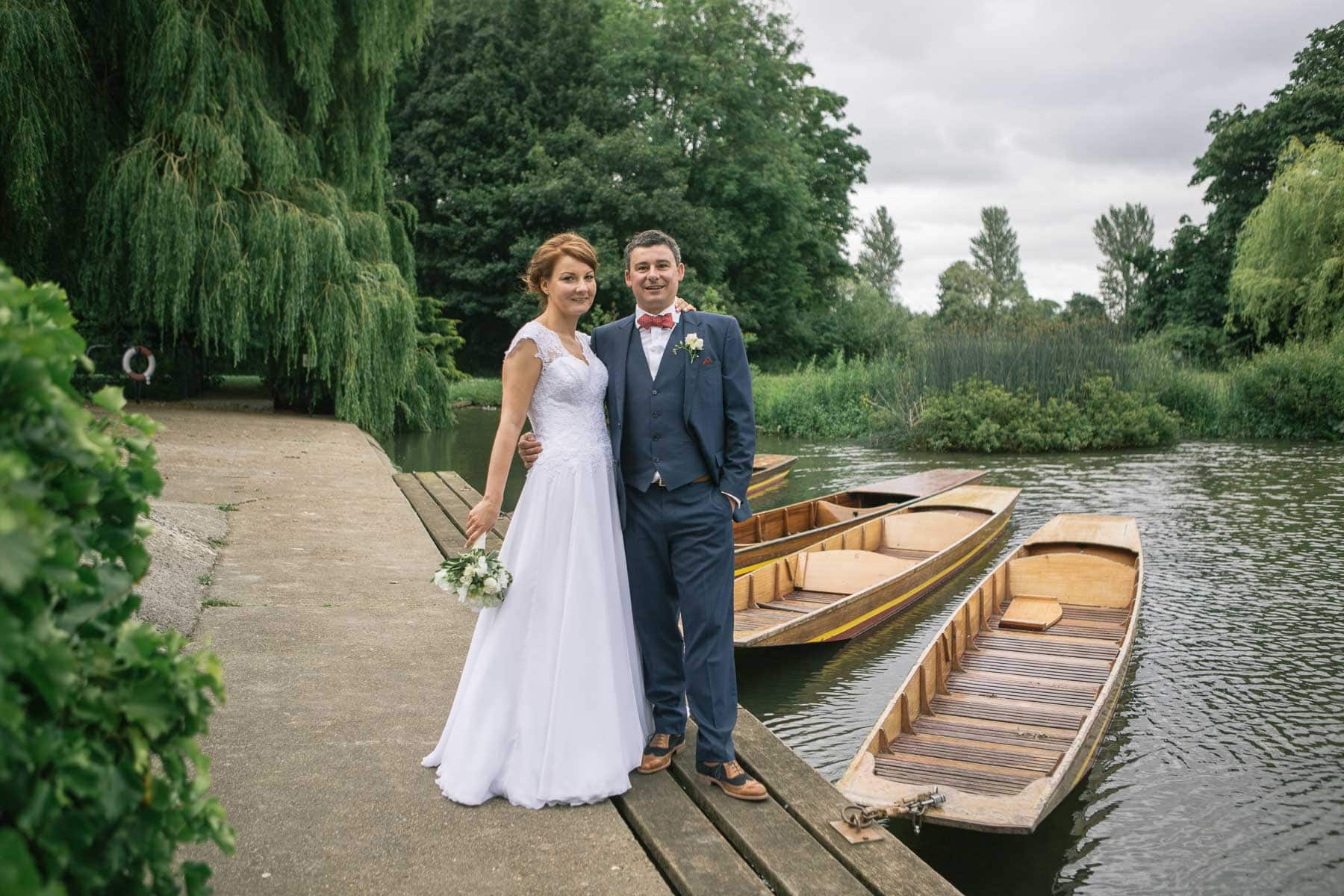 Bride and groom stand next to punts on the river