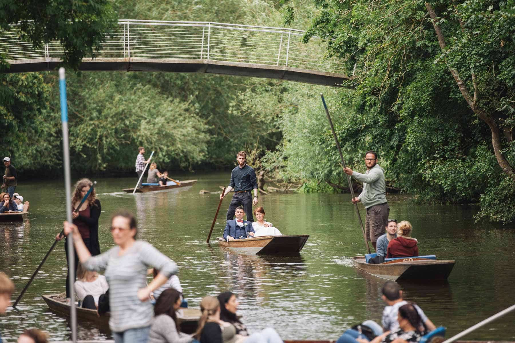 The river is full of punts, bride and groom arrive on one of them
