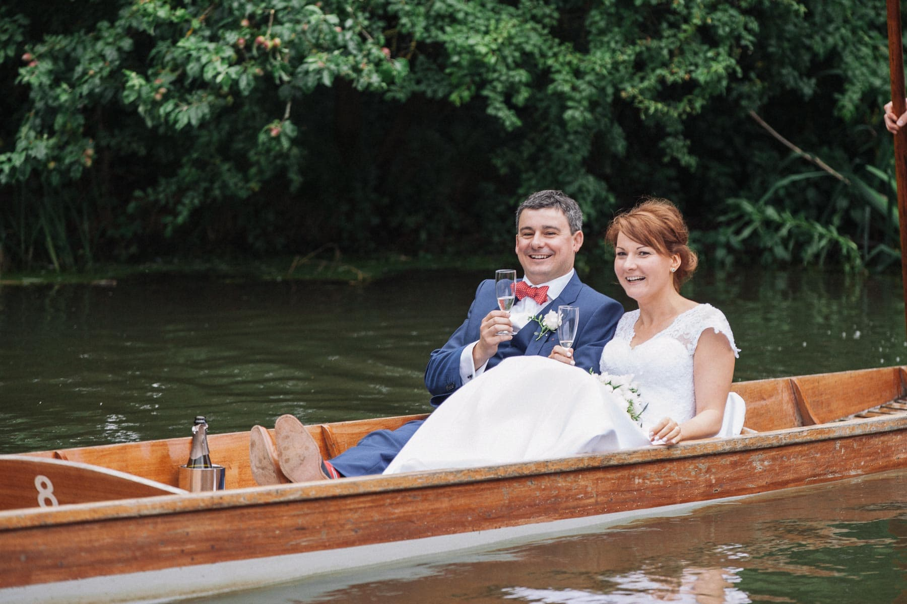Close up of bride and groom on their punt, with champagne