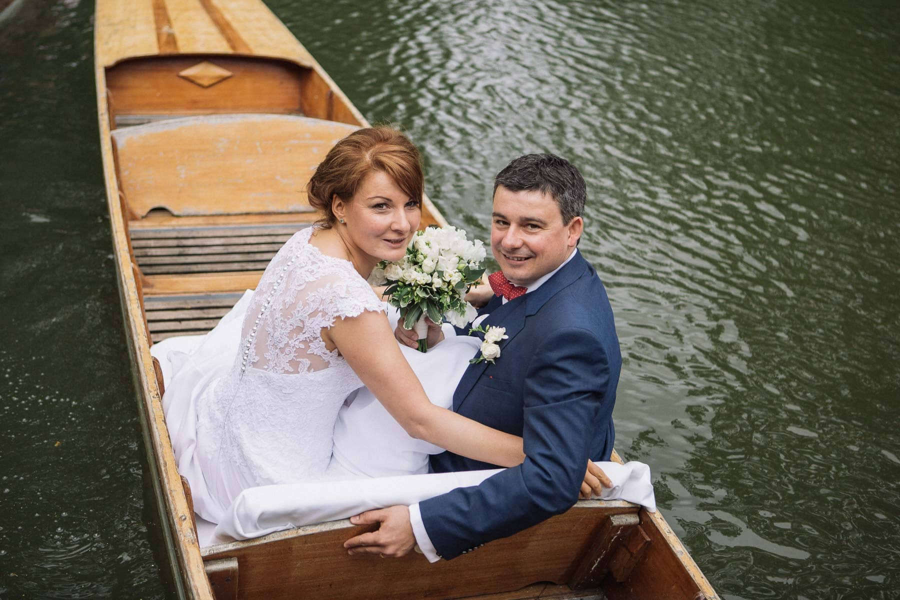 Bride and groom embrace on punt