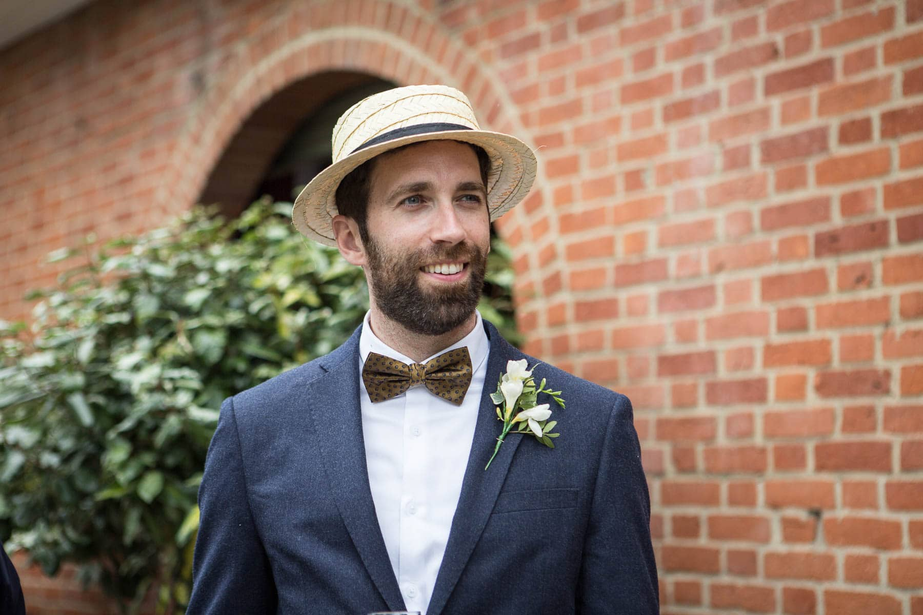 An usher in a bowtie and straw boater