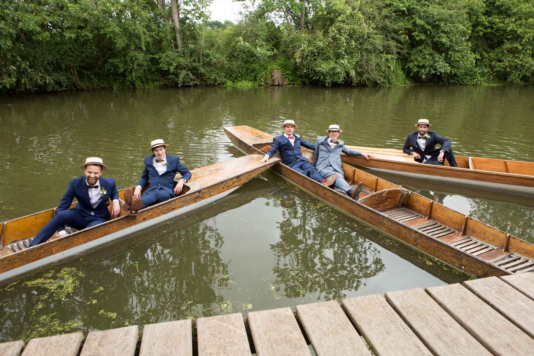 The groomsmen recline in punts on the river wearing straw boaters