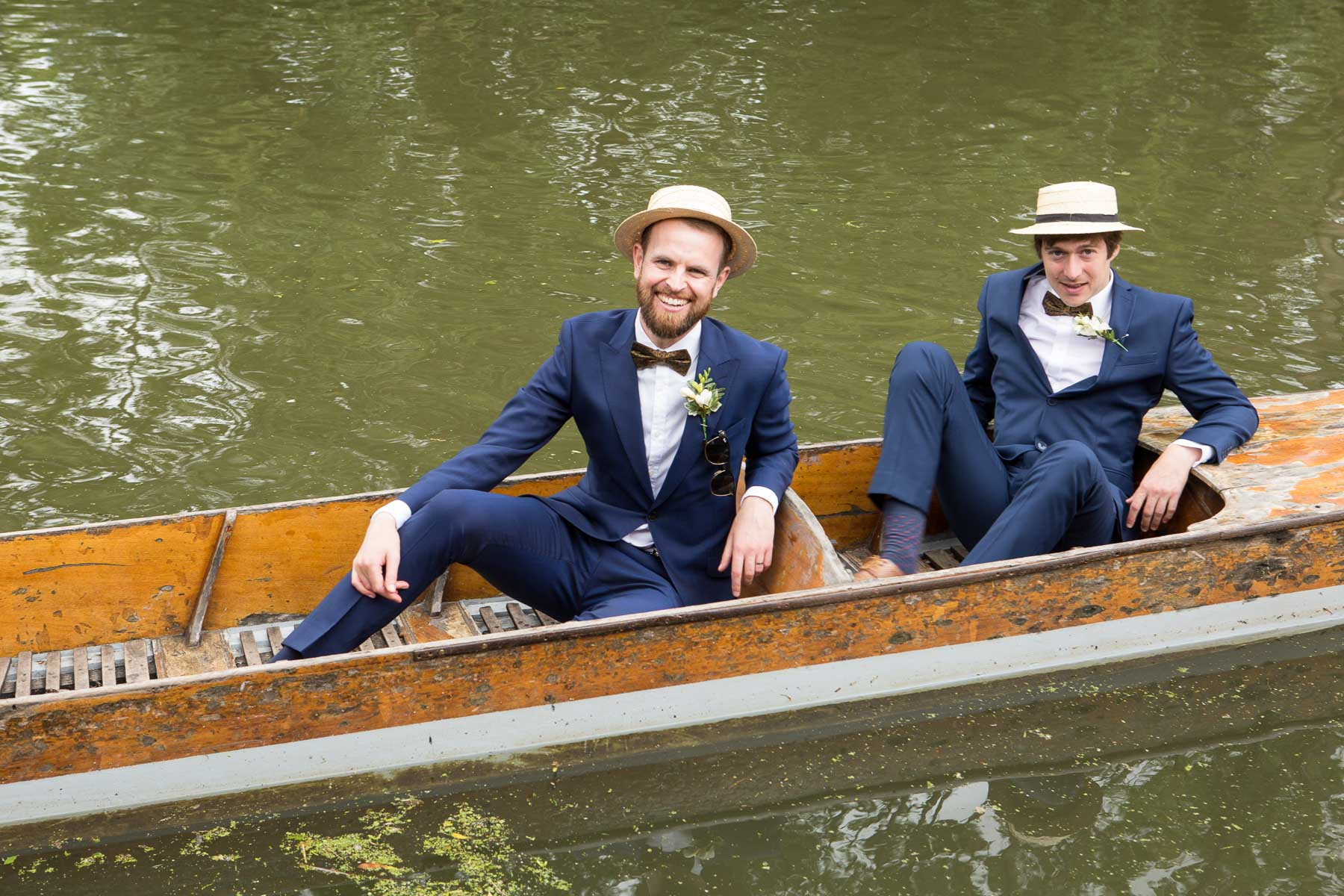 Two of the groomsmen in a punt, wearing straw boaters